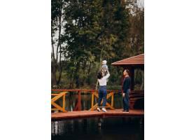 年轻的家庭带着年幼的儿子走在河边的桥上_11601188