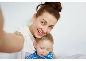 年轻的母亲和她一岁的小儿子穿着睡衣摆姿势_10271275
