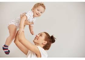 年轻的母亲在床上玩耍她的小婴儿_10271378