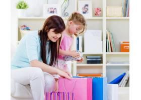 年轻的母亲带着年幼的女儿在家购物室内_10880326