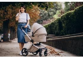 年轻的母亲推着婴儿车在公园里散步打电话_10298569