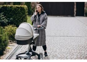 年轻的母亲推着婴儿车在公园里散步打电话_7869473