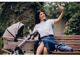 年轻的母亲推着婴儿车坐在公园的长凳上_10298563