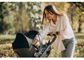 年轻的母亲推着婴儿车走路_11601293