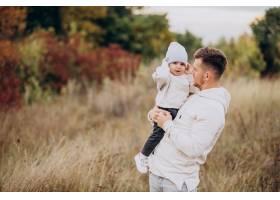年轻的父亲带着年幼的儿子在田里_10703517