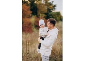 年轻的父亲带着年幼的儿子在田里_10703526