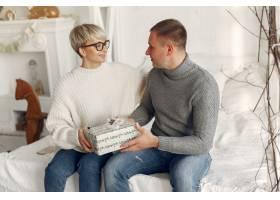 家人在家里圣诞装饰品附近的情侣穿灰色_10704859