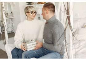 家人在家里圣诞装饰品附近的情侣穿灰色_10704861