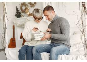 家人在家里圣诞装饰品附近的情侣穿灰色_10704865