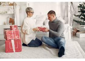 家人在家里圣诞装饰品附近的情侣穿灰色_10704872