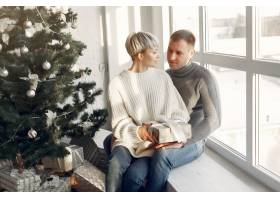 家人在家里圣诞装饰品附近的情侣穿灰色_10704892