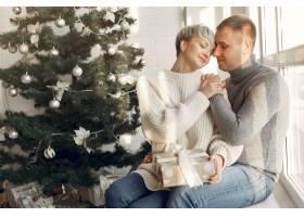 家人在家里圣诞装饰品附近的情侣穿灰色_10704894