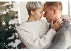 家人在家里圣诞装饰品附近的情侣穿灰色_10704903