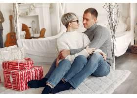 家人在家里圣诞装饰品附近的情侣穿灰色_10704939