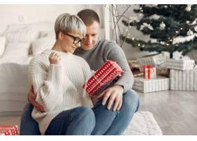 家人在家里圣诞装饰品附近的情侣穿灰色_10704940