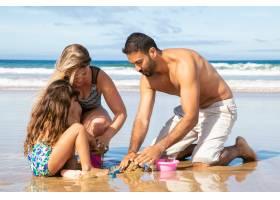 小女孩和爸爸妈妈一起在海上度假在湿沙上_11072704