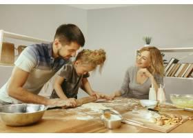 可爱的小女孩和她漂亮的父母在家里的厨房里_12699592