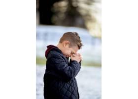 一个小男孩站在公园里在模糊背景的阳光下_10583379
