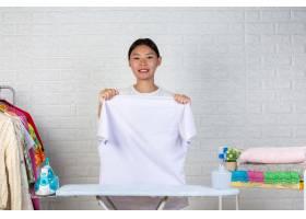 一个年轻的女佣正用一块白砖在她的熨衣板上_5491613