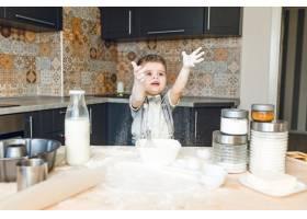 一个有趣的孩子站在一个玫瑰色的厨房里玩面_9860711