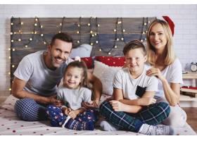 一家人在床上度过圣诞节早晨的肖像_11756975