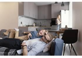 中等镜头的父亲和孩子坐在沙发上_13436798
