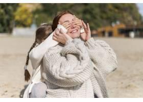 中镜头微笑的母亲和孩子在海滩上_11105715
