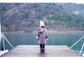一个可爱的小女孩站在青绿色的湖边的木制码_10835523