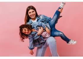 一个迷人的女人和小女儿在粉色背景上玩耍_12431971