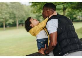 一个非裔美国孩子和他的父亲在公园里玩耍_11819360