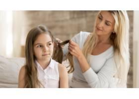 一位年轻的母亲在家里给女儿编辫子_10604657
