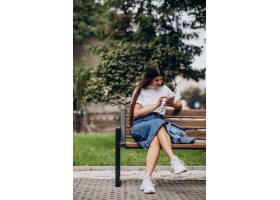 一名年轻女子坐在公园的长凳上使用电话_10298565