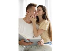 一名女子亲吻她男朋友的脸颊_10697442