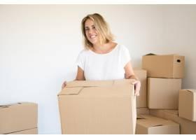 一名金发高加索女子在新房或公寓里提着纸箱_10579188