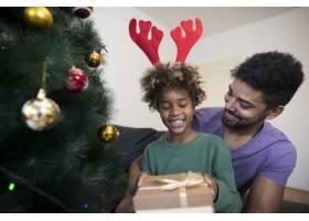 站在圣诞树旁打开礼品盒的女孩看起来很惊讶_11036445