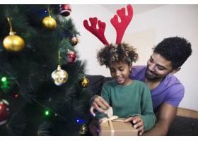 站在圣诞树旁的女孩站在父亲的怀抱中打开_11036474