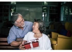 笑容满面的老公惊喜地给妻子送礼盒_4107900