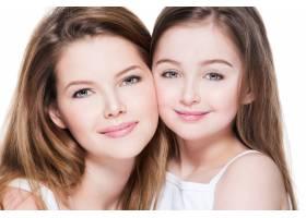 美丽幸福的年轻母亲带着8岁的小女儿在演播_11180595