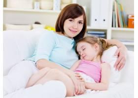 美丽快乐的年轻母亲带着睡着的小女儿坐在家_10626331