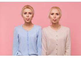 美丽的年轻金发双胞胎的肖像做着鬼脸露出_10787307