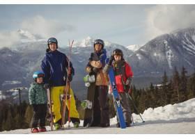 身着滑雪服的一家人站在积雪的阿尔卑斯山上_11184848
