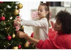 迷人的女孩和妈妈在装饰圣诞树_11776136