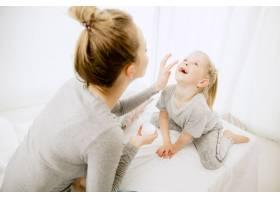 阳光明媚的早晨年轻的母亲和她的小女儿在_12701986