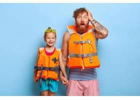 水平拍摄惊叹的红头发父亲穿着橙色充气救生_12349235