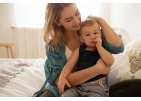 温柔快乐的年轻金发妈妈坐在卧室里腿上抱_11193325