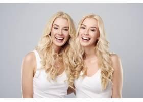 灰色背景上的欢笑双胞胎_12470081