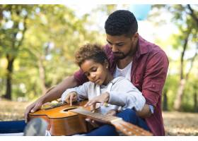 父亲和女儿在一起弹着吉他_11138556