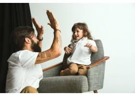 父亲和年幼的儿子在家里的起居室里玩耍年_10444882