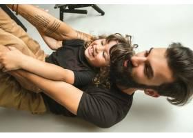 父亲和年幼的儿子在家里的起居室里玩耍年_10444888