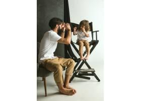 父亲和年幼的儿子在家里的起居室里玩耍年_12699677